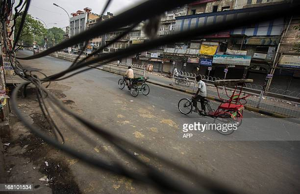 Two Indian rickshaw pullers ride past sagging power lines without customers in the Old Quarters in New Delhi on May 5 2013 The ruling Indian...