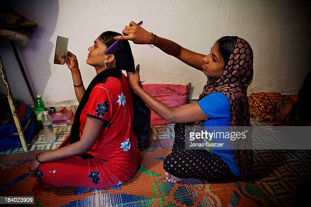 Two Indian surrogate mothers help each other with the daily routines in their room located in a Mumbai ghetto A clinic in Mumbai called Surrogacy...