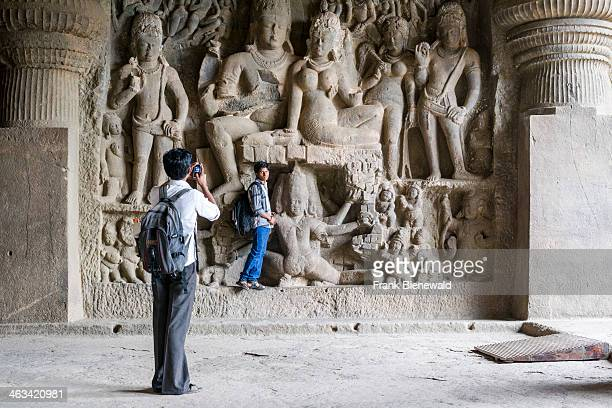 Two indian tourists taking photographs of each other inside cave 29 the Dhumar Lena Cave in the UNESCO World Heritage site Ellora All the temples are...