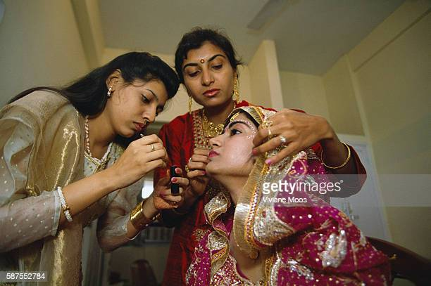 Two Indian women apply makeup to a bride in preparation for her arranged marriage