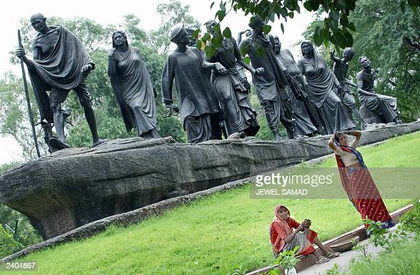 Two Indian women take a break from cleaning a statue which commemerates the Salt March of 1930 and features Indian leader Mahatma Gandhi leading a...