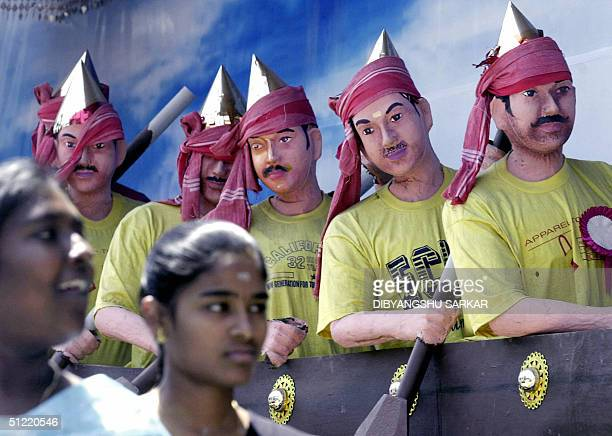 Two Indian youths walk past a display featuring traditional oarsmen in Madras 26 August 2004 The display is based upon the harvest festival in the...