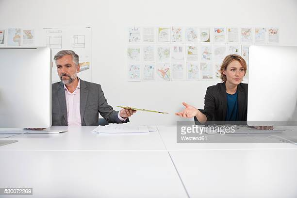 Two indifferent colleagues at their desks in an office