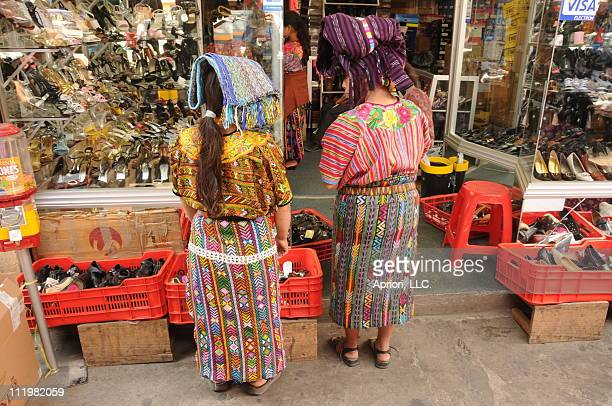 Two indigenous women scan the selection of shoes near the Democracia market in Xela Guatemala