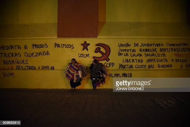 Two indigenous women stand near protester painted graffities on February 112016 at the San Cristobal de Las Casas cathedral which will be visited by...