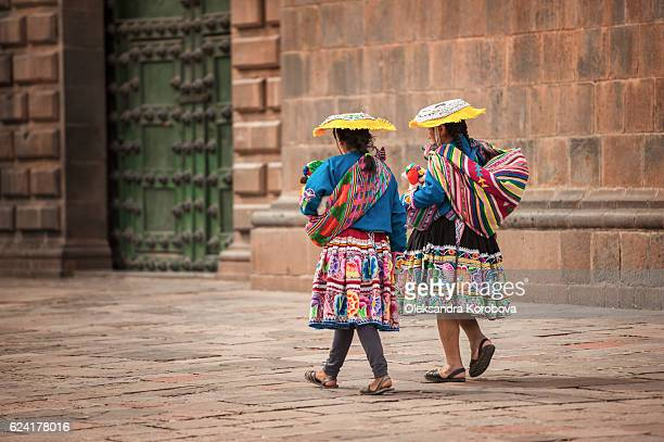 Two indigenous women walking in the city square of Cusco, Peru.