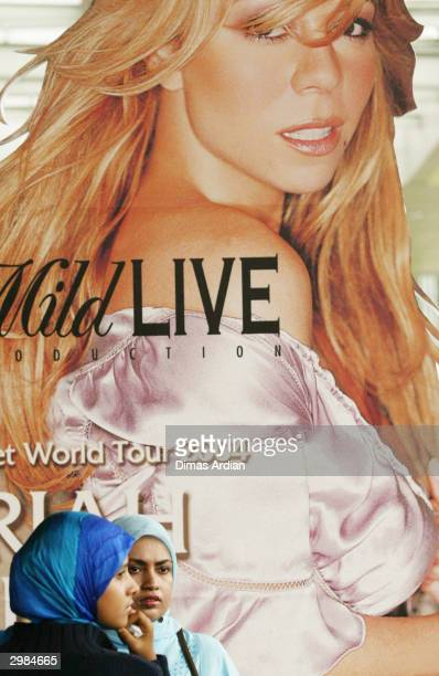 Two Indonesian muslim girls stand in front of a poster of American pop diva Mariah Carey at the Jakarta Hilton Convention Centre on Sunday February...