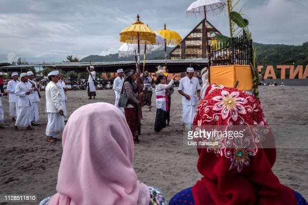 Two Indonesian Muslim women watching as Hindu devotees pray during the Melasti ritual ceremony at Parangkusumo beach on March 3 2019 in Yogyakarta...