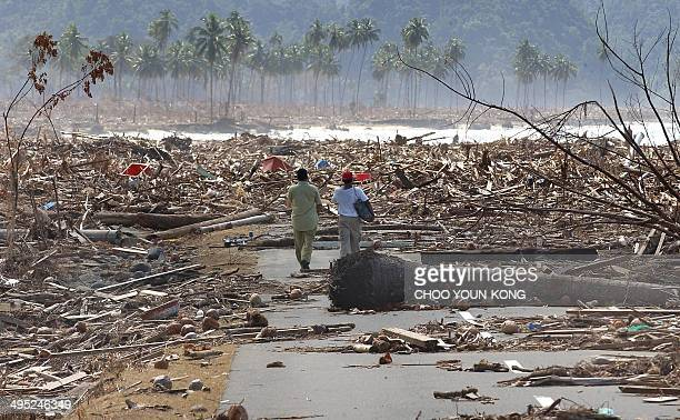 Two Indonesian refugees walk down a road covered with debris leftover from the tsunami disaster as they return to look for their homes in the west...