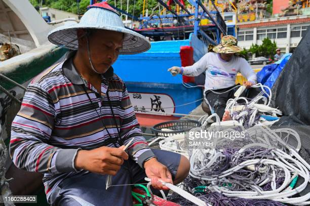 Two Indonesian workers sort out fishing nets at the typhoon shelter at Nanfangao harbour in Suao Yilan county as Typhoon Lekima approaches off the...