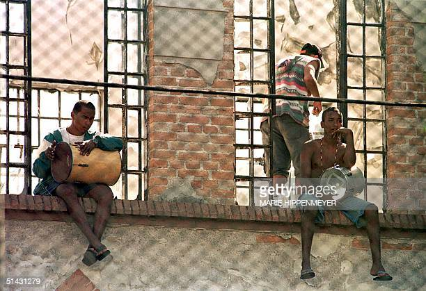 Two inmates at the juvenile detention center known as 'Febem' beat on drums at the windows of one of the jail's pavilions 05 May 1999 during the...