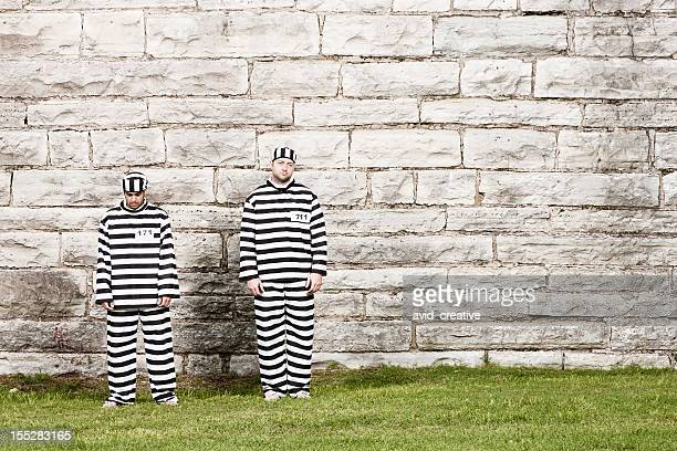two inmates stand in front of prison wall - uniform stockfoto's en -beelden