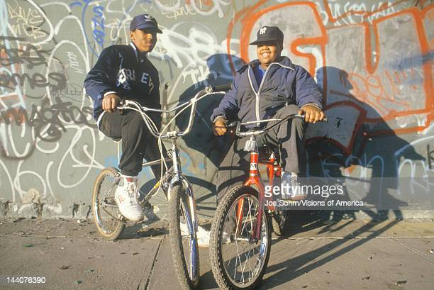 Two innercity AfricanAmerican teenagers on bicycles NY City