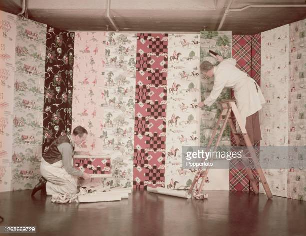 Two interior decorators attach a selection of wallpapers printed with contemporary designs to display panels at a trade exhibition in England in 1951