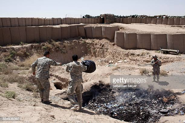 """Two interpreters for Bravo troop dump their trash in the base's """"burn pit."""" Bravo """"Bonecrusher"""" Troop of the 1-75 Cavalry, 101st Airborne Division..."""