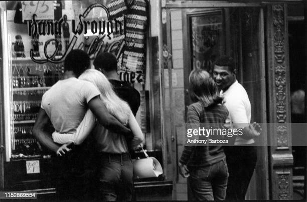 Two interracial couples and an additional man stand in front of a jewelry store window in the Greenwich Village neighborhood New York 1960s