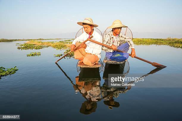 Two Intha fishermen fishing on wooden boats