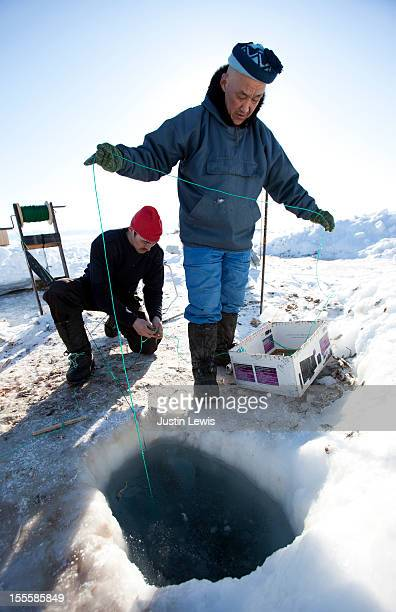 two inuit males ice fishing in norhthern greenland - inuit stock pictures, royalty-free photos & images