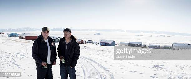 two inuit males in front of town-qaanaaq greenland - inuit stock pictures, royalty-free photos & images