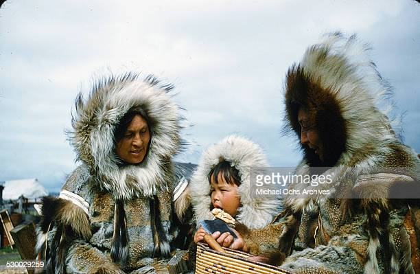 Two Inuit women and a baby pose in fur coats in Unalakeet Alaska