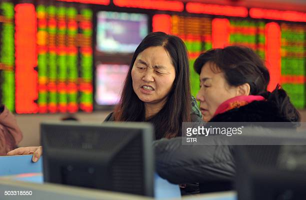 Two investors chat in a stock firm in Fuyang east China's Anhui province on January 4 2016 Trading on the Shanghai and Shenzhen stock exchanges was...