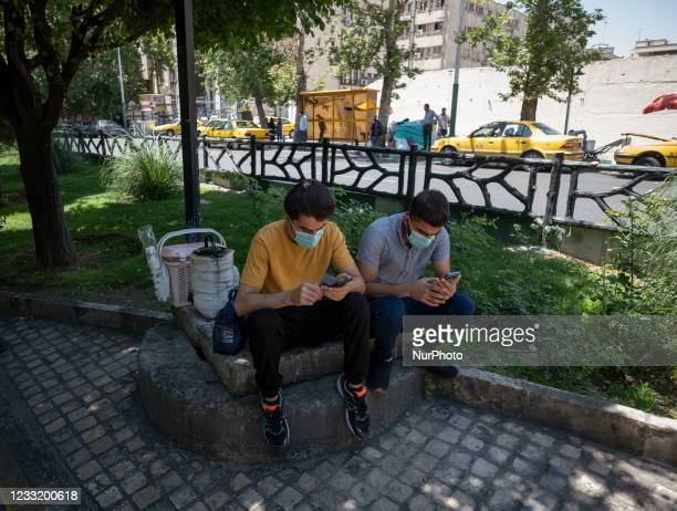 Two Iranian men wearing protective face masks use their smartphones while sitting on a street-side in downtown Tehran on May 30, 2021. Iranians will...