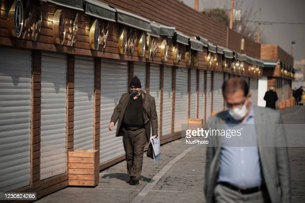 Two Iranian men wearing protective face masks walk past closed fast-food shops near Tehrans Traditional Grand bazaar amid the COVID-19 outbreak in...