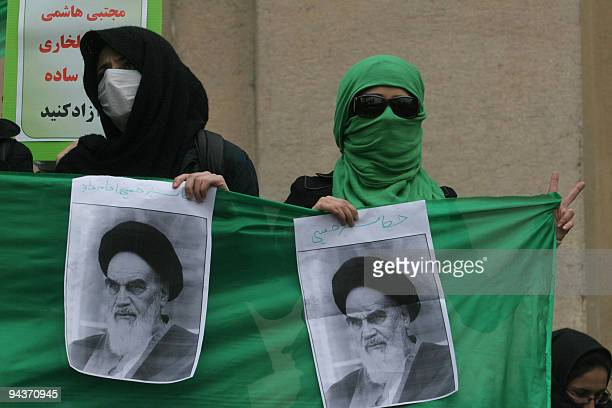 Two Iranian opposition supporters hold pictures of the late founder of the Islamic republic Ayatollah Ruhollah Khomeini as they protest with the...