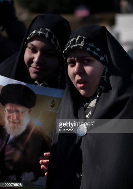 Two Iranian veiled women hold a portrait of Irans Supreme Leader Ayatollah Ali Khamenei while taking part a rally to mark the Islamic Revolution...