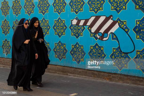 Two Iranian women walk past a wall mural of a gun outside the former US embassy in Tehran Iran on Sunday Aug 5 2018 Irans central bank acting on the...