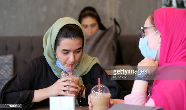 Two Iranian women wearing protective face masks sit at a cafe in northern Tehran, following the new coronavirus outbreak in Iran, August 9, 2020.