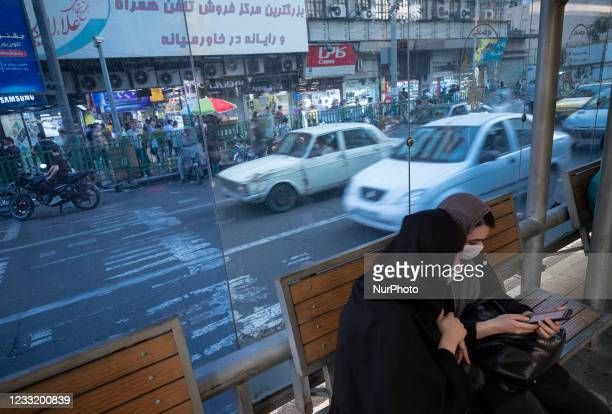 Two Iranian women wearing protective face masks use a smartphone while sitting at a bus-stand near a crossroad in downtown Tehran on May 30, 2021....