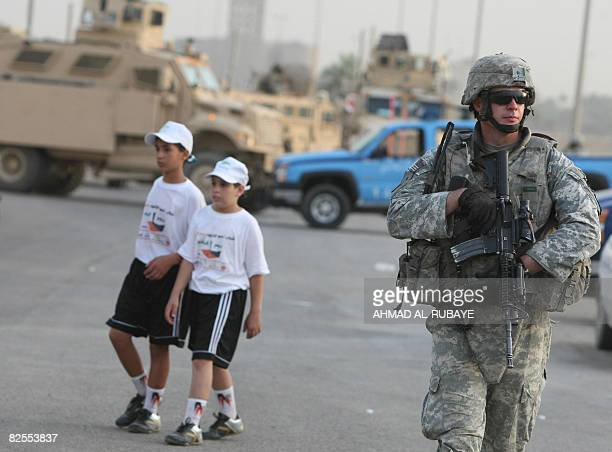Two Iraqi boys dressed for the Karrada festival walk past a US soldier during the commercial neighbourhood's annual festival in the Iraqi capital...