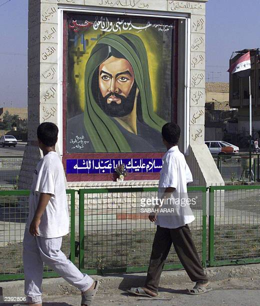 Two Iraqi boys look at a new painting for Imam Hussein Ibn Ali the sonlaw of Islam's prophet Mohammed on a main street in the mainly Shiite Muslim...