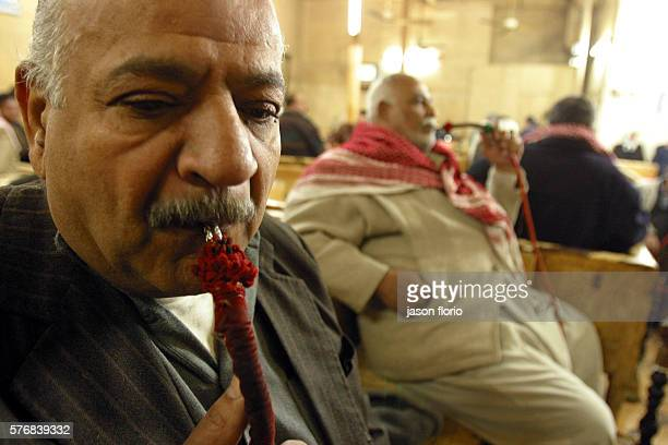 Two Iraqi men smoke shisha pipes at the Sharia Raschid cafe At the Sharia Raschid cafe poets writers and journalists meet to exchange materials ideas...