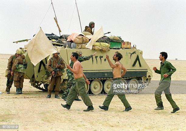 Two Iraqi soldiers wave the white flag as they surrender to Egyptian forces 25 February 1991 somewhere in Kuwaiti desert on the second day of the...