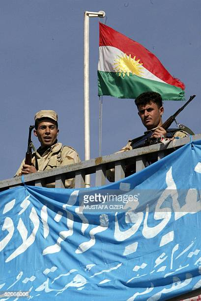 Two Iraqi Special Forces policemen stand guard near a Kurdistan flag during a press conference given by the leader of Kurdistan Democratic Party...