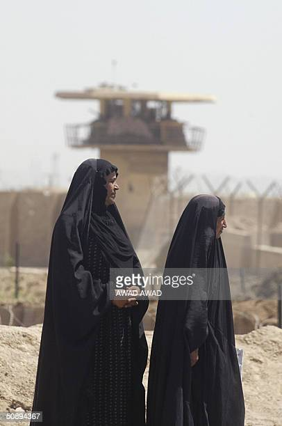 Two Iraqi women stand outside the Abu Ghraib prison west of Baghdad as others take part in day two of a three day sitin by families in tents set up...