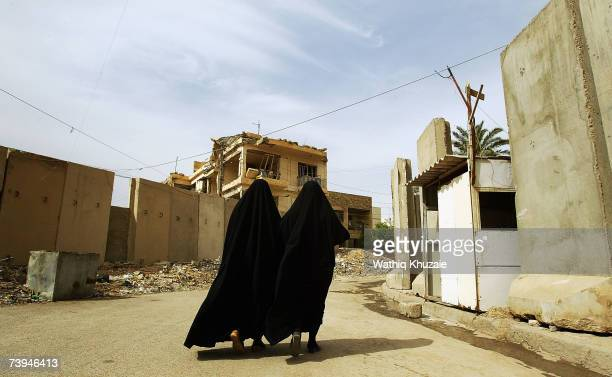 Two Iraqi women walk near a blast wall on April 22 2007 in the Karrada neighborhood of Baghdad Iraq US troops are building a wall that the military...