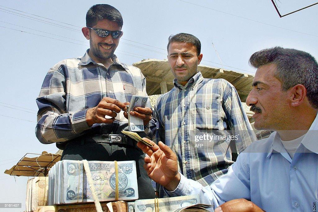 Two Iraqis Exchange Iraqi Dinars For Us News Photo
