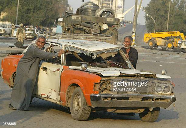 Two Iraqis push a destroyed taxi away from the site of a massive truck bomb explosion at the main entrance to the USled coalition headquarters in...