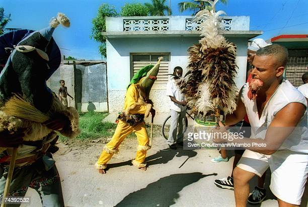 Two 'Ireme' or 'Diablito' dance the 'Efori Isun' with a 'Nianigo' who holds the head of a chicken in his mouth at a ceremony to consecrate the street...
