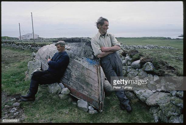 Two Irish men lean against an old wooden boat next to a stone wall in a rural area on Tory Island Ireland