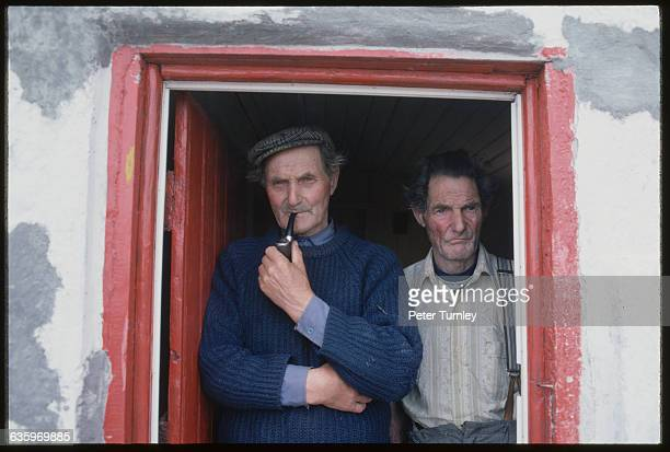 Two Irish men one smoking a pipe stand together in a doorway of a building on Tory Island Ireland
