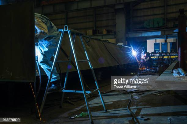 Two Iron Workers Welding In A Shipbuilding Factory Stock Photo