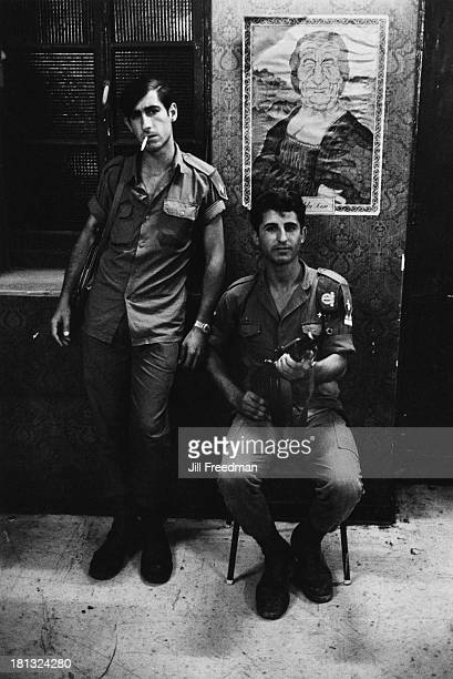 Two Israel Defense Forces soldiers pose underneath a caricature of Golda Meir a month after the Six Day war Jerusalem Israel July 1967
