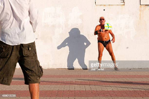 two men playing matkot in tel aviv, israel - old man in speedo stock photos and pictures