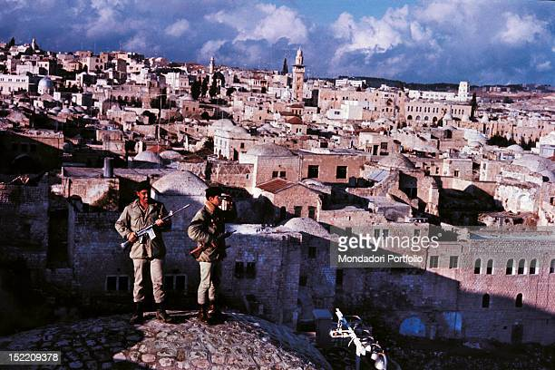 Two Israeli soldiers armed and with binoculars patrolling from above the situation in the Old City in Jerusalem where the areas most sacred for Jews...