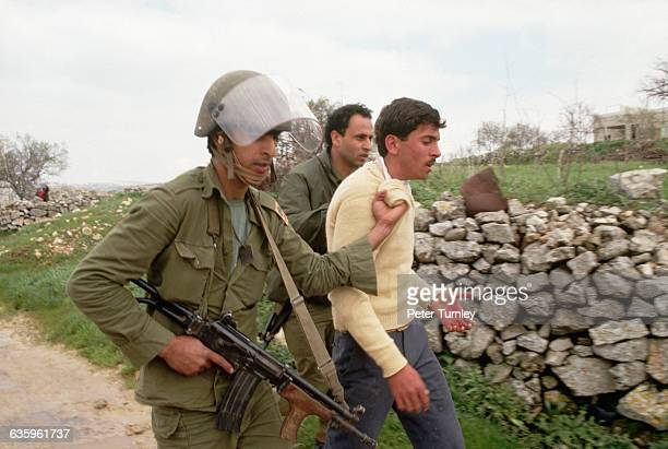 Two Israeli soldiers force a bleeding Palestinian man to walk with them down an unpaved road