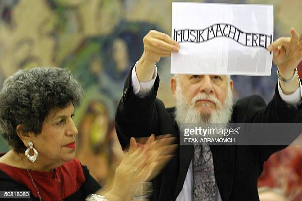 Two Israelis react against the awarding of the Wolf Prize to Argentinianborn Israeli pianist and conductor Daniel Barenboim holding a banner in...